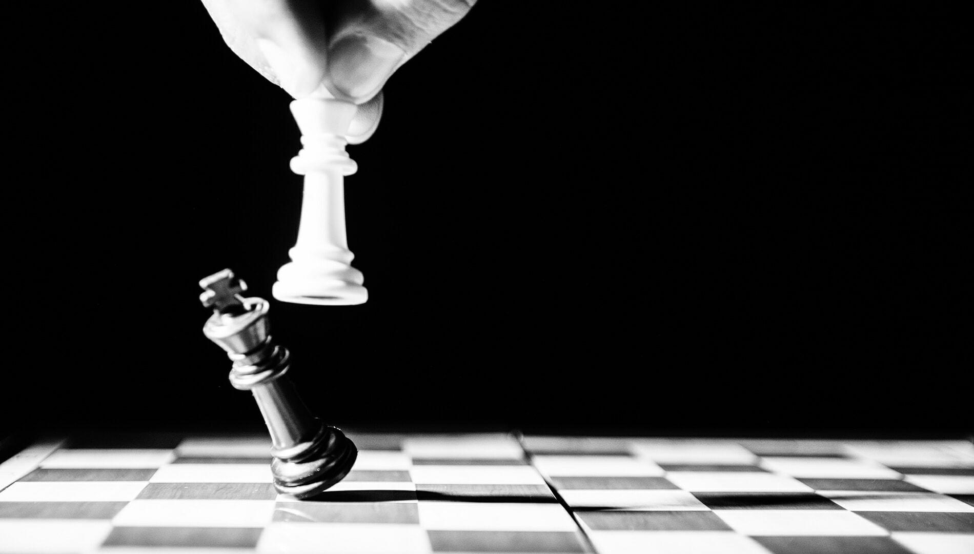 White king chess piece knocking down a black king piece