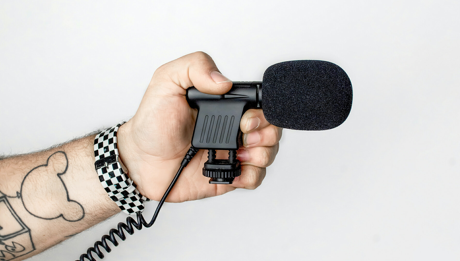 Hand microphone on a man's hand with tattoos and black-and-white wrist watch