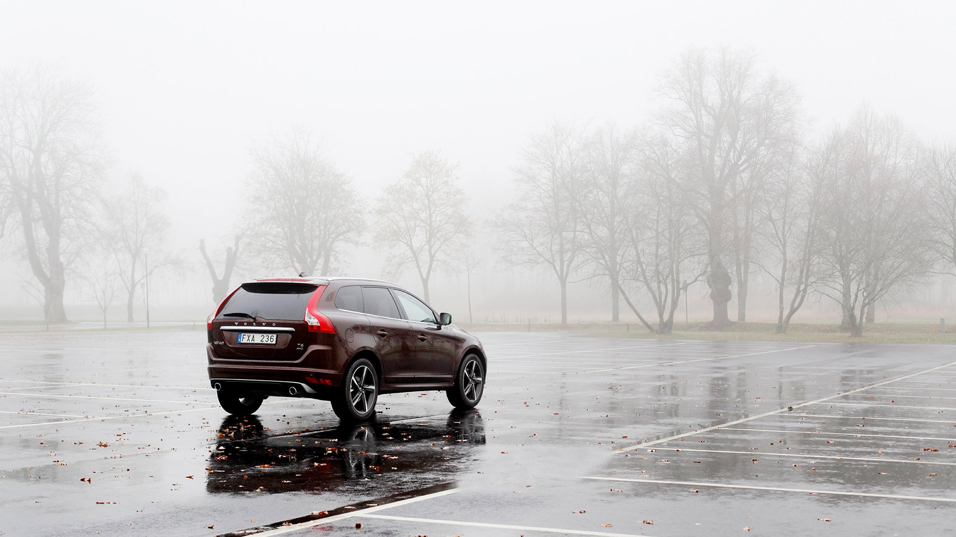 Volvo XC60 on an empty parking lot on a grey rainy day