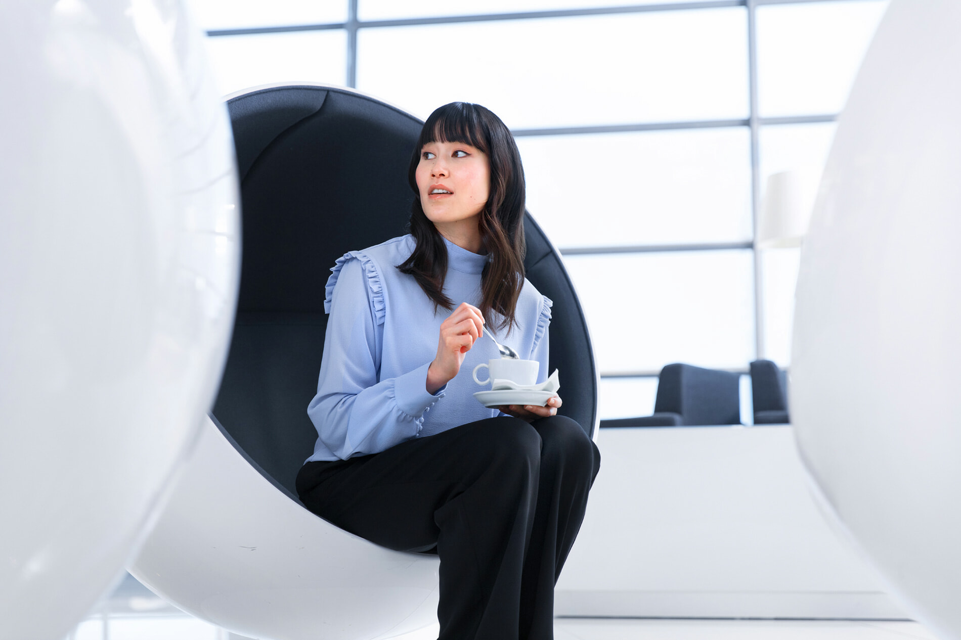 Asian woman resting coffee on her lap on a Eero Aarnio Ball chair at Finnair lounge