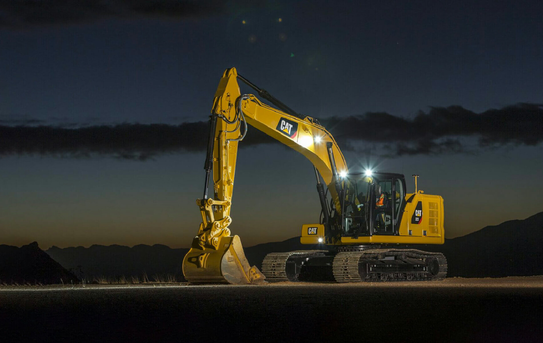 Yellow Caterpillar hydraulic shovel at night time with headlights on