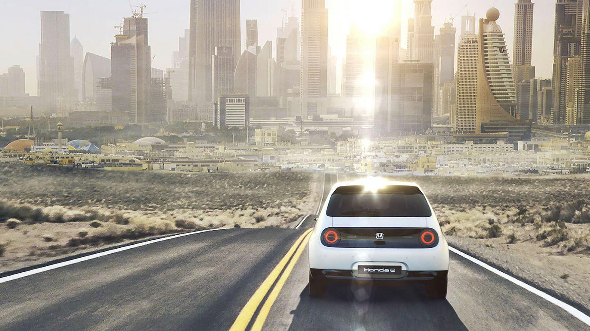 White Honda E car driving to futuristic looking city