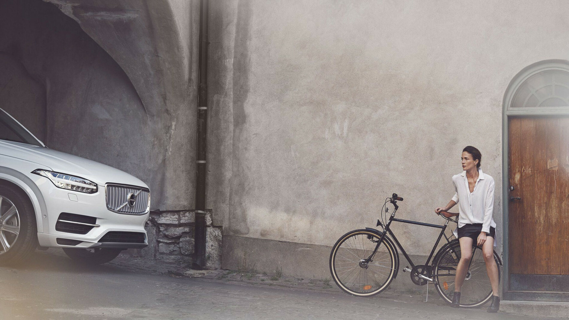 Woman sitting on a back of bicycle watching white Volvo car going by